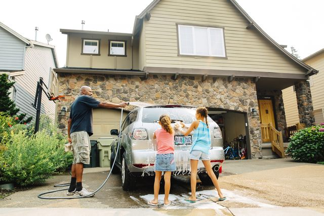 father and daughters washing car