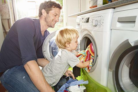 padre e hijo sacan ropa de una lavadora
