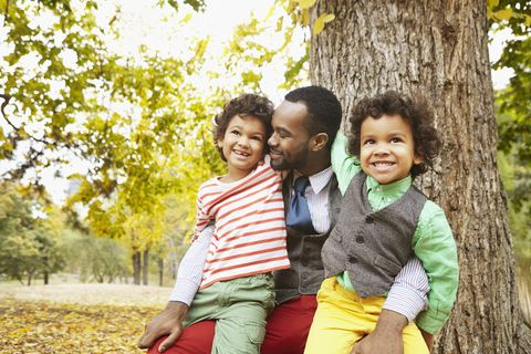 Father and sons smiling in park