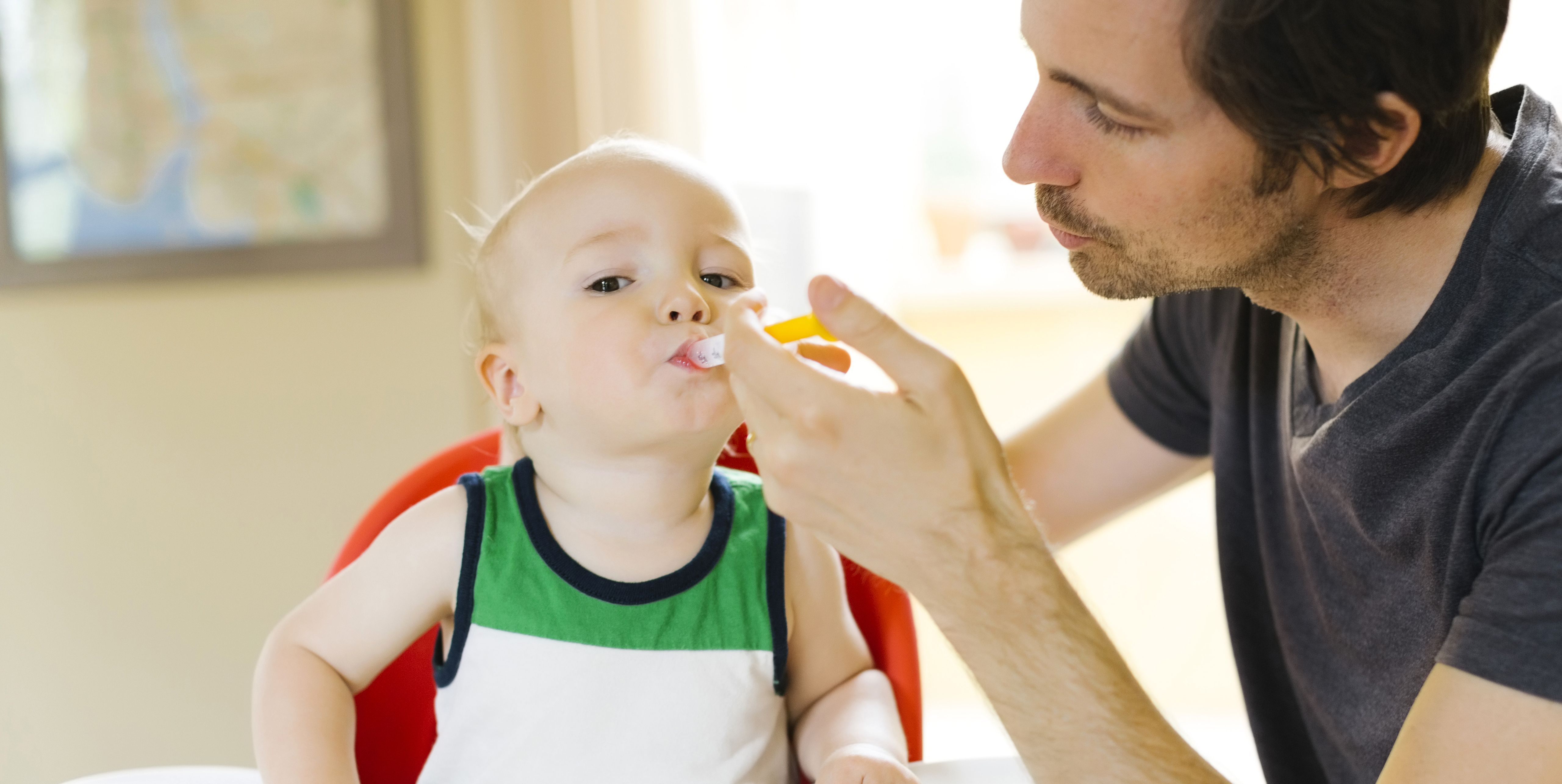 Father applying medicine to son (12-17 months)