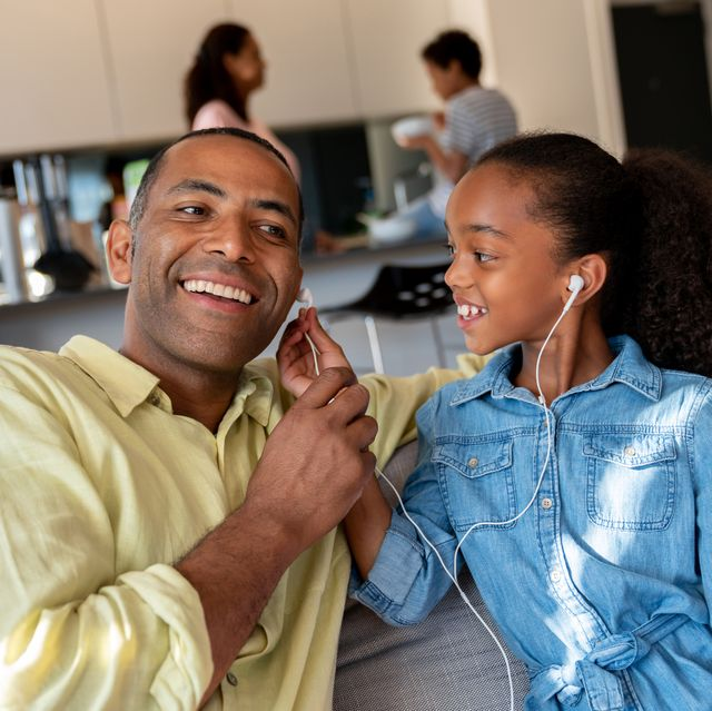 portrait of a happy father and daughter listening to music with headphones on a tablet computer and smiling   lifestyle concepts
