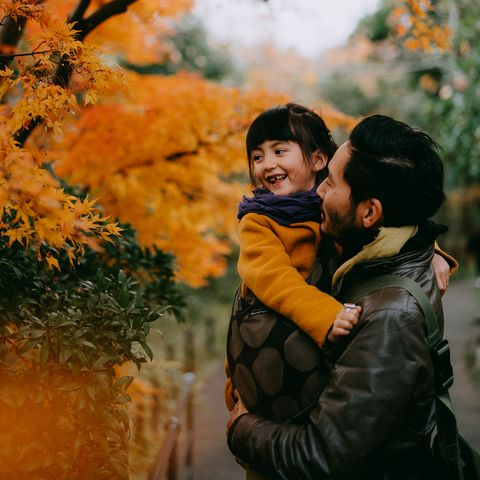man with child in autumn leaves