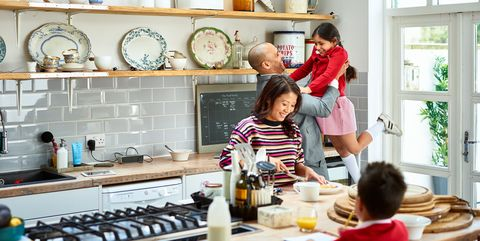 father lifting daughter and smiling as mother makes breakfast