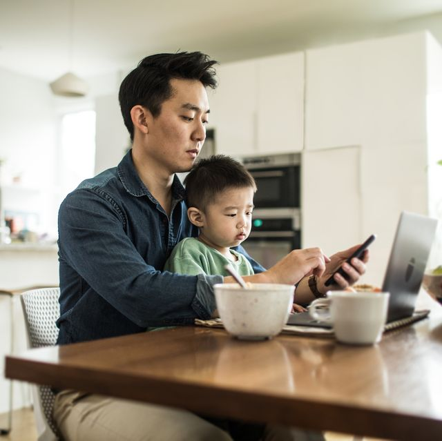 father multi tasking with young son 2 yrs at kitchen table