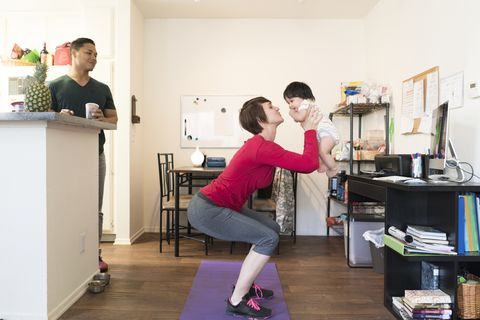 Father watching mother doing squats with baby in arms
