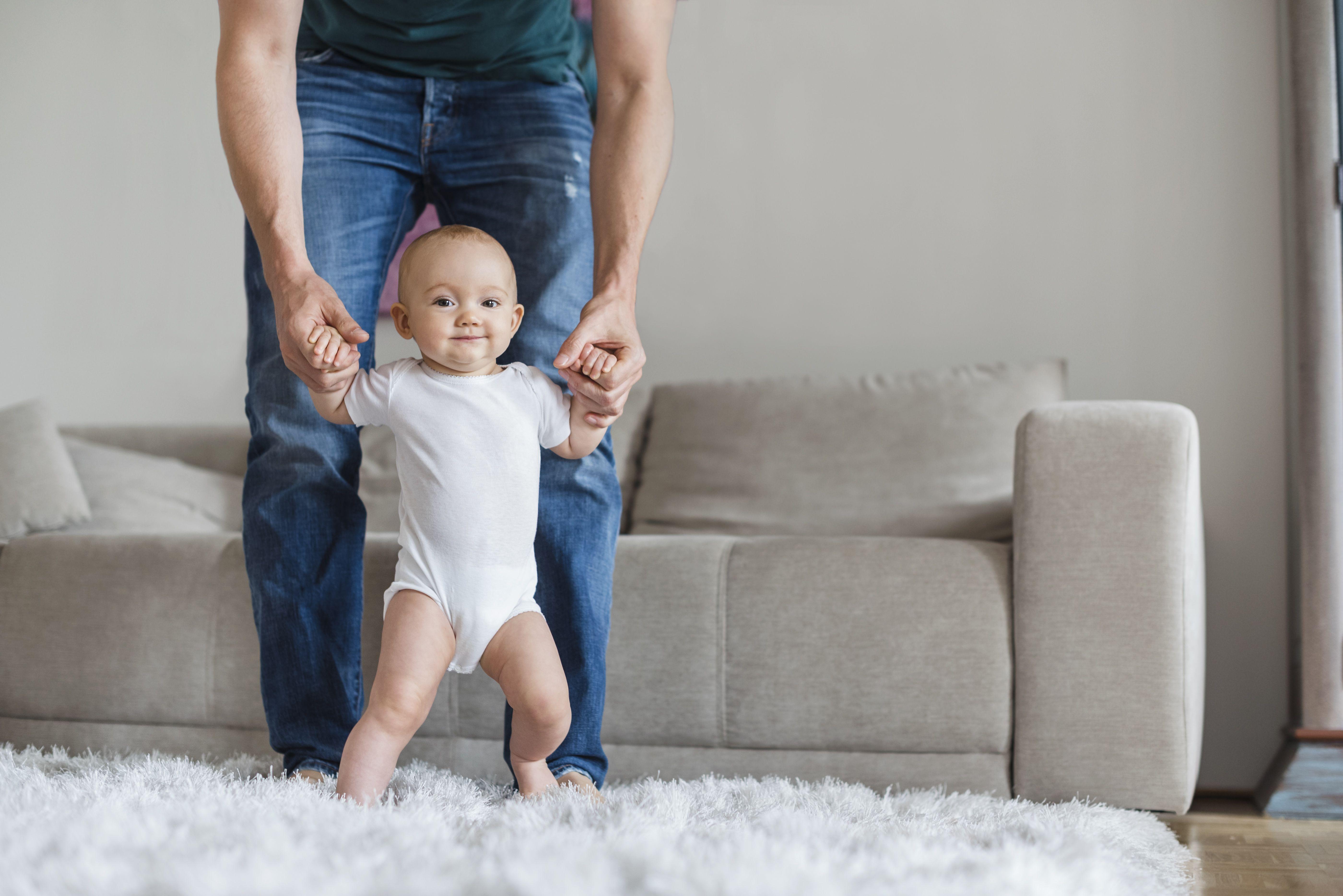 Bebé caminando con ayuda de su padre