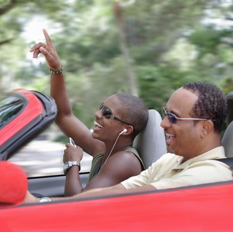 father and son ride in red convertible