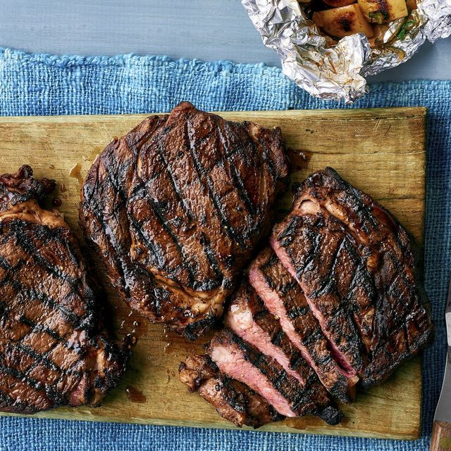 grilled rib eyes on wood board with blue linen and foil packet