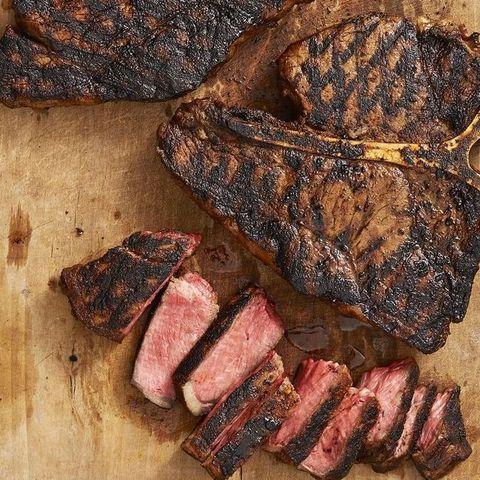 cajun t bone steaks whole and sliced on wood board