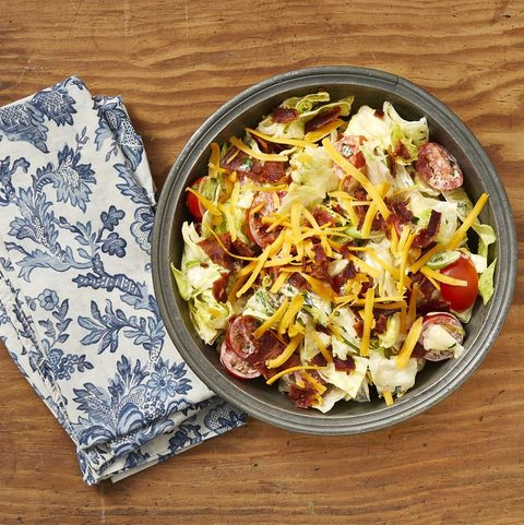 ranch chopped salad in metal bowl with blue floral napkin on wood