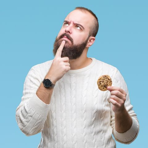 Young hipster man eating chocolate chips cookie over isolated background serious face thinking about question, very confused idea
