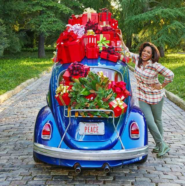 oprah standing next to a vintage blue beetle car loaded with red holiday gifts