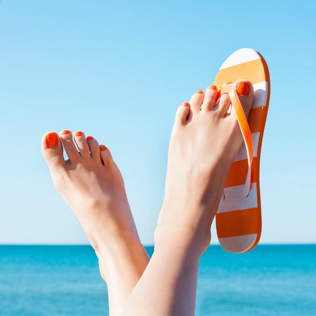 feet with flip flops dangling in sun