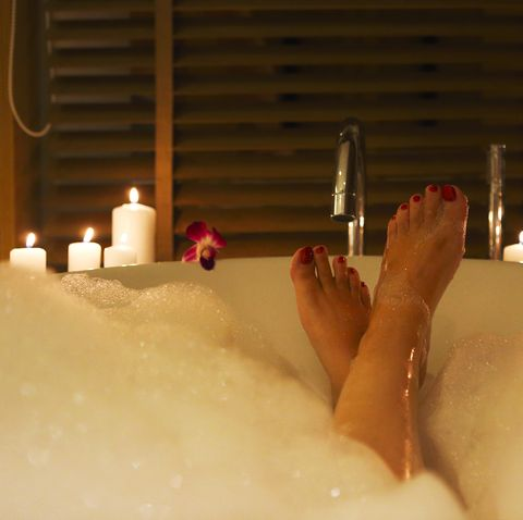 feet of the young woman in bath with foam and candles