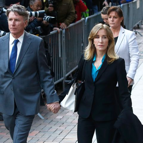 felicity huffman walking on a street outside the courthouse in a black suit