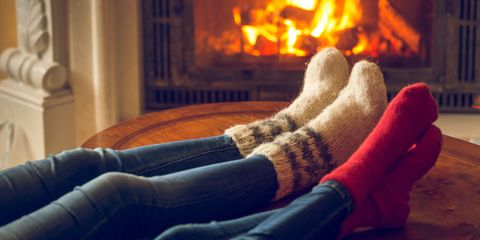 Female and male feet in wool socks warming at fireplace