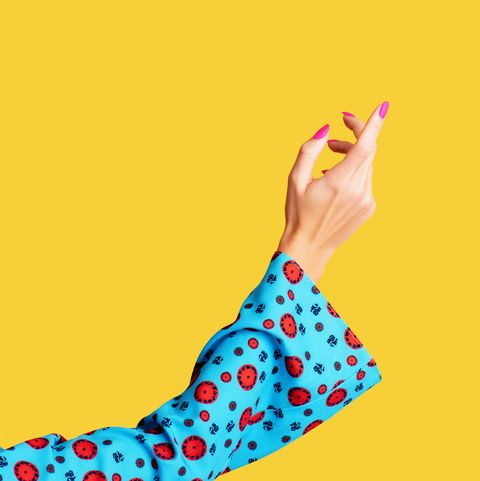 female arm and hand on yellow background