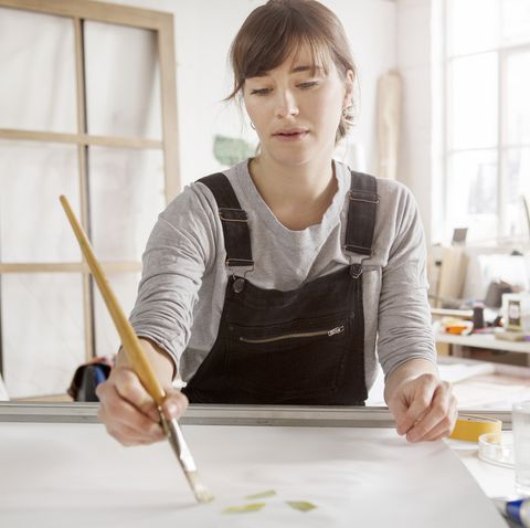 hobbies for women - Female artist paints in studio.