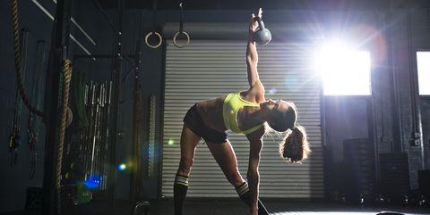 Female Athlete Doing Exercise Using Kettle Bells In Gym