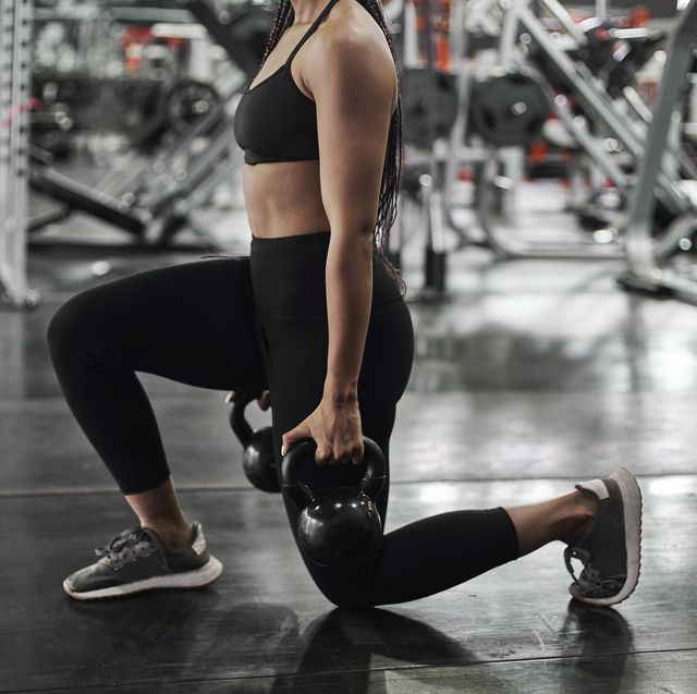 female athlete doing lunges with kettlebells