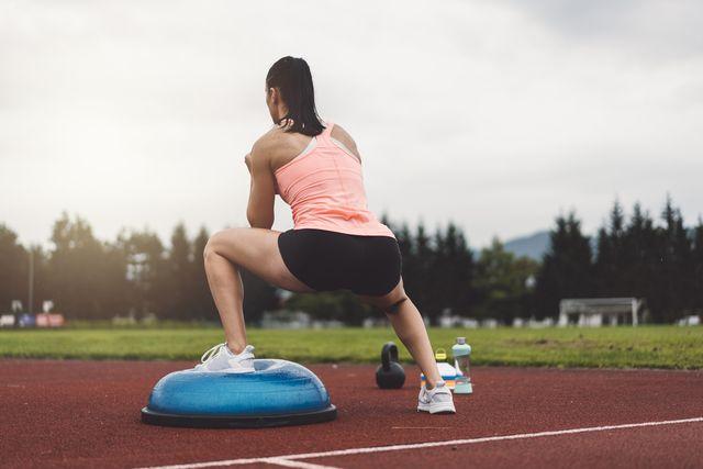 una atleta si allena all'aperto con una bosu ball