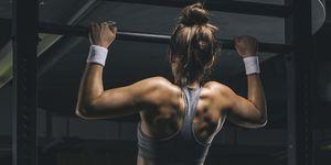Female athlete exercising chin-ups
