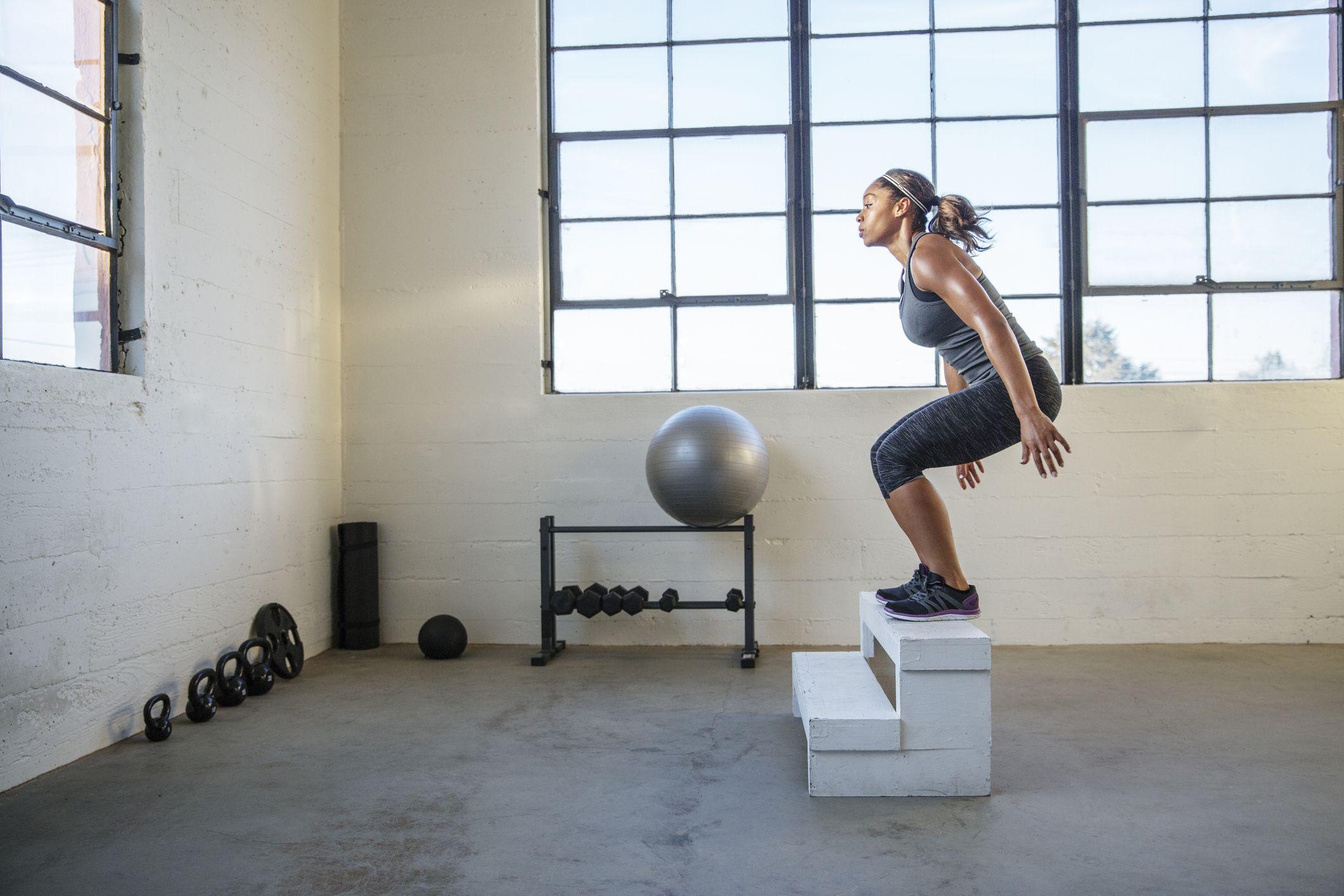 naissportlane jõusaalis puidust istmele hüppamas