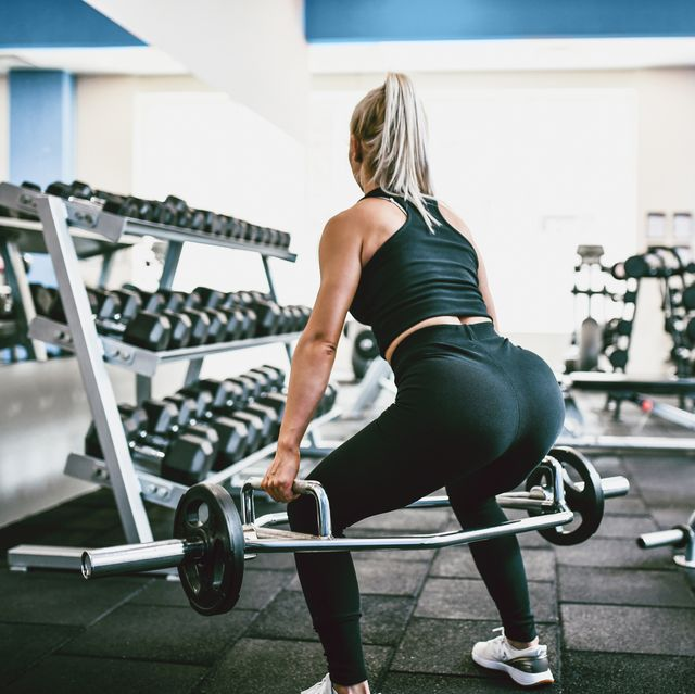 female athlete practicing deadlift in gym