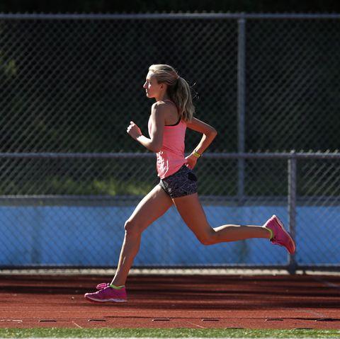 a female athlete runs on a track