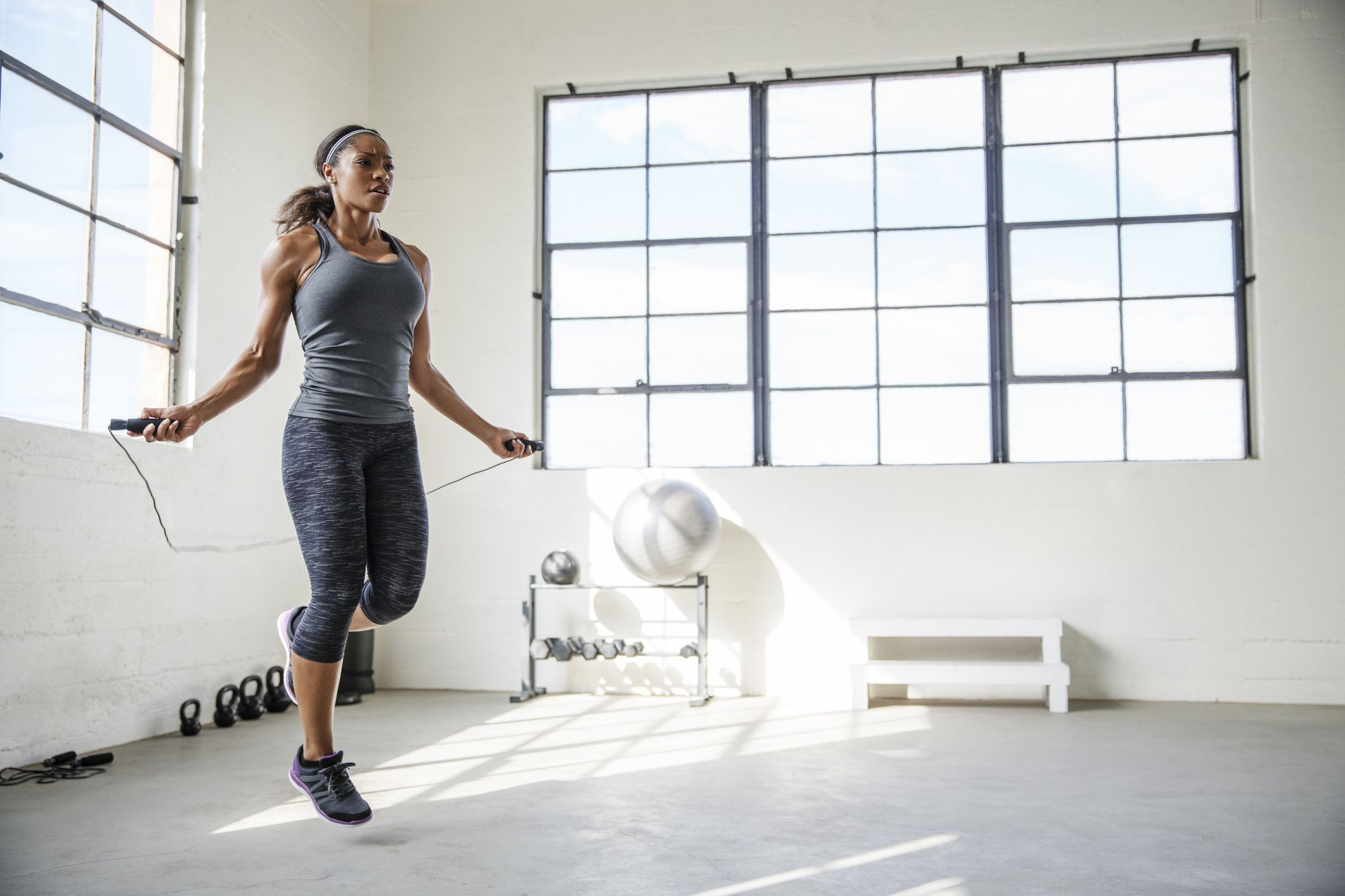 jõusaalis hüppenööriga hüppav naissportlane