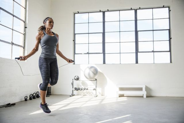 female athlete skipping with jumping rope in gym