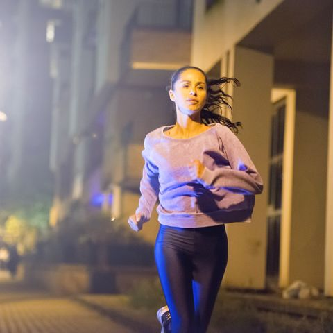 female athlete, urban setting at night