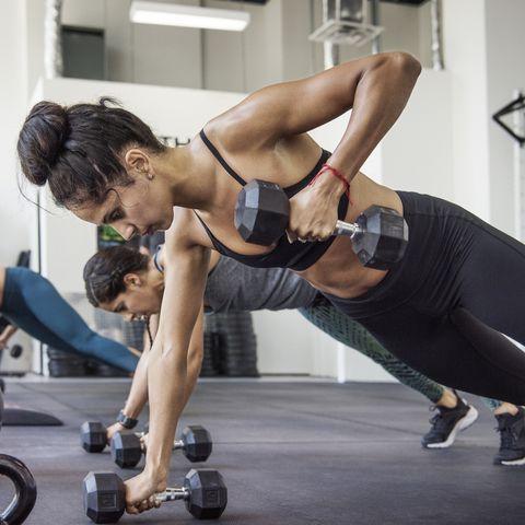 Female athletes doing push-ups using dumbbells in crossfit gym