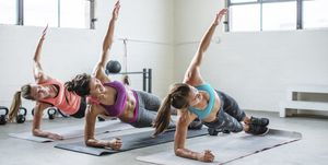 Female athletes doing side plank pose in gym
