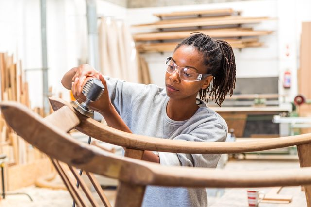 female black worker restoring an old chair in a woodworking studio