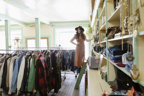 Female business owner working, arranging display in vintage shop