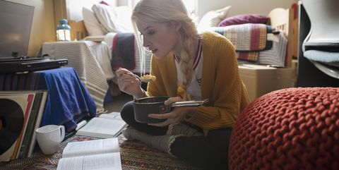 Female college student eating and studying on floor in dorm room
