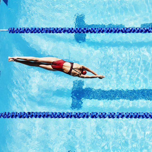 una mujer se lanza de cabeza a una piscina para empezar a nadar