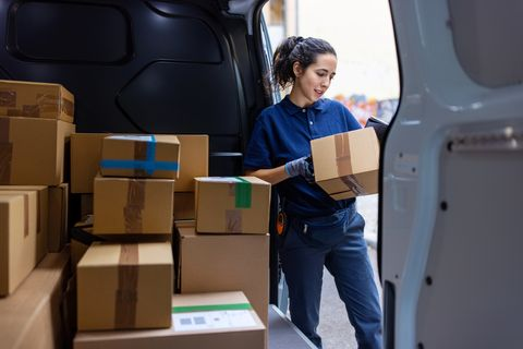 female courier checking the parcel for delivery