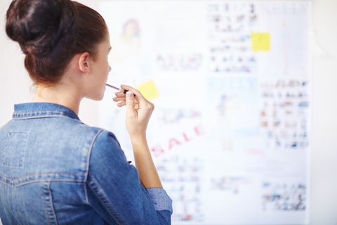 Female creative professional thinking in front of whiteboard