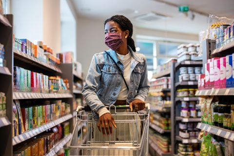 A female customer buys a mask at a grocery store.