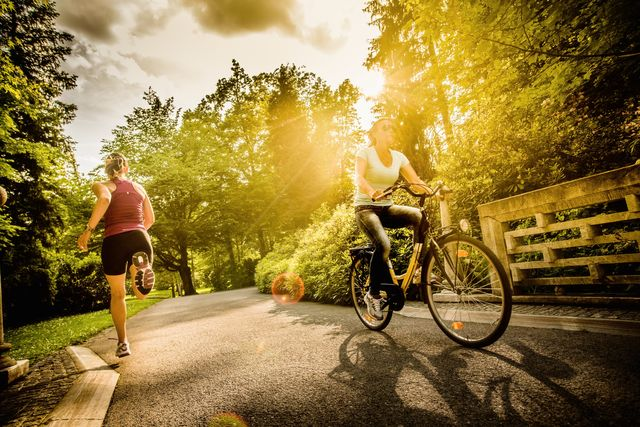 female cyclist and jogger in a park