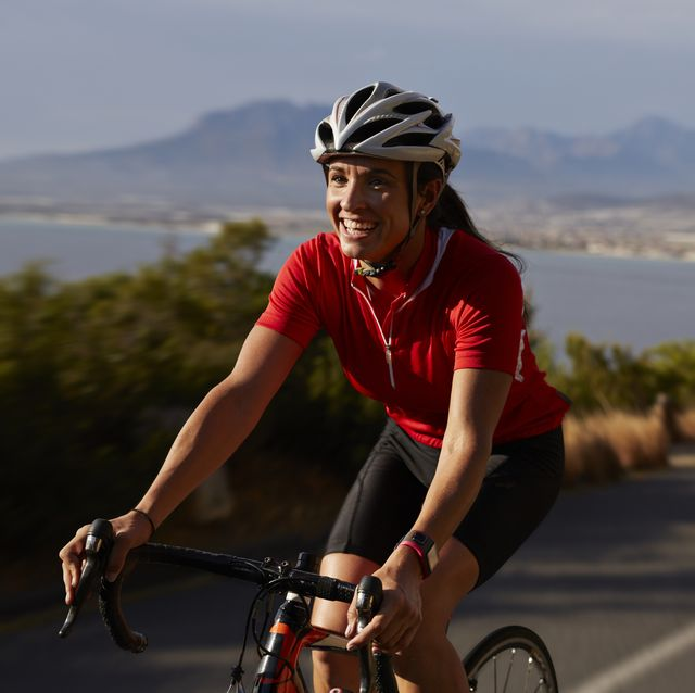female cyclist going uphill on roadbike and laughing