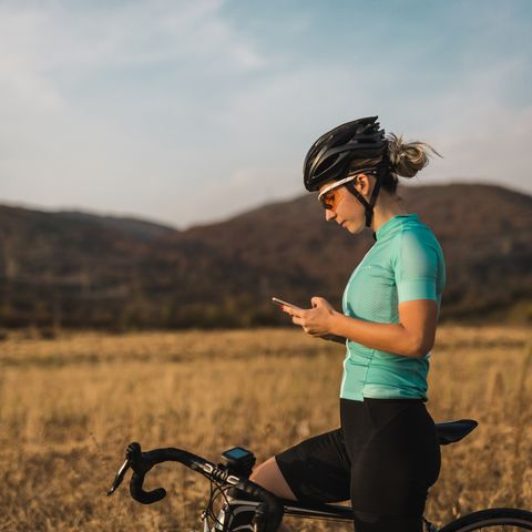 female cyclist looking gps navigation on smartphone