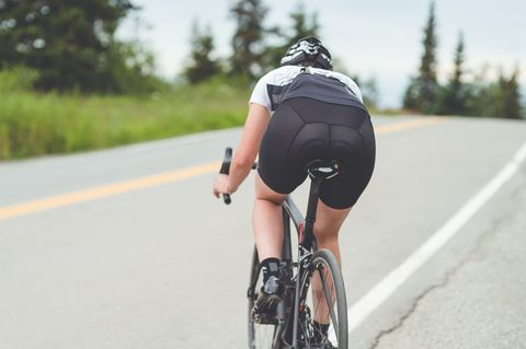 Female cyclist rides along a rural highway