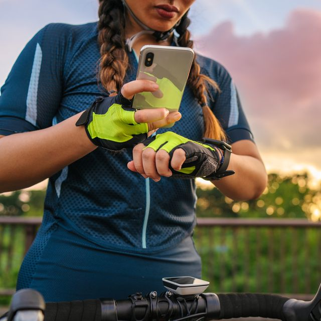 female cyclist setting up her smart watch and smart phone before cycling