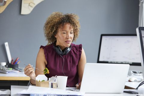 female designer eating working lunch and looking at laptop at desk