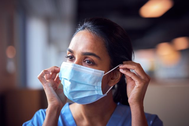 female doctor in scrubs putting on face mask