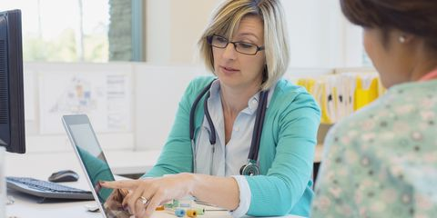 Female doctor reviewing medical records with nurse at desk