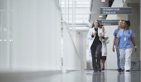 Female doctors discussing while walking in hospital corridor